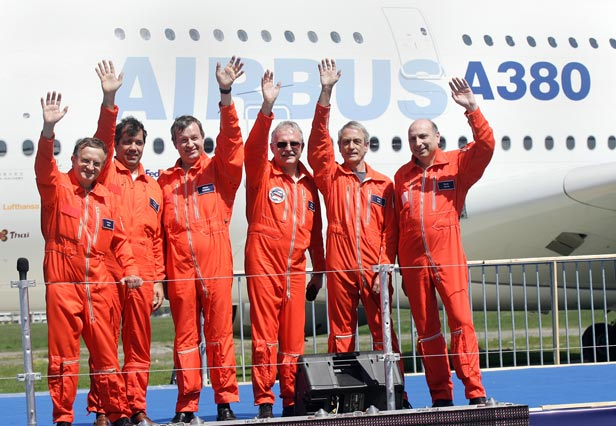 The crew of the Airbus A380 wave to spectators after completing the plane's maiden flight.