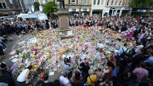 Crowds look at the floral tributes after a minute's silence in St Ann's Square, Manchester