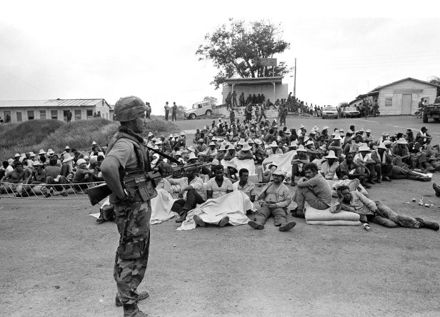 A soldier stands guard over a group of Cuban prisoners captured during the military action on the island of Grenada.