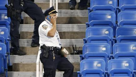 Police investigate after a drone, seen to the right of the officer in the white shirt, crashed into the Louis Armstrong Stadium during a tennis match (AP)