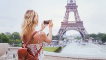 Woman photographing Eiffel Tower