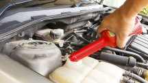 Stock image of a person pouring additive into car radiator tank