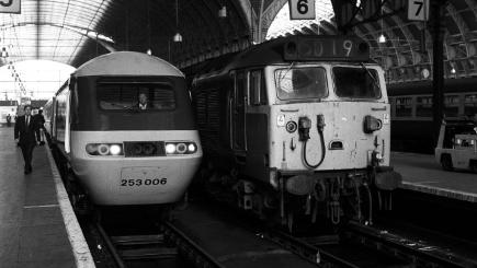 A new Inter-City 125 pulls into Paddington station alongside one of the older diesel trains.