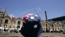 Sky writing 'sorry' watched by man in Australian flag hat