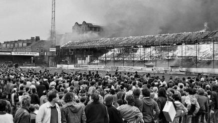 Supporters evacuated from the stands look on as fire rages.