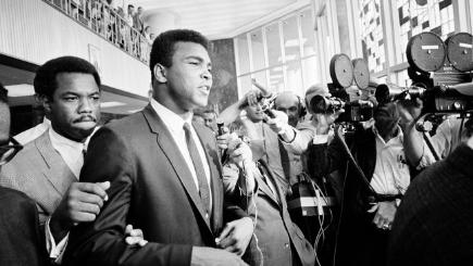 Muhammad Ali surrounded by press and supporters