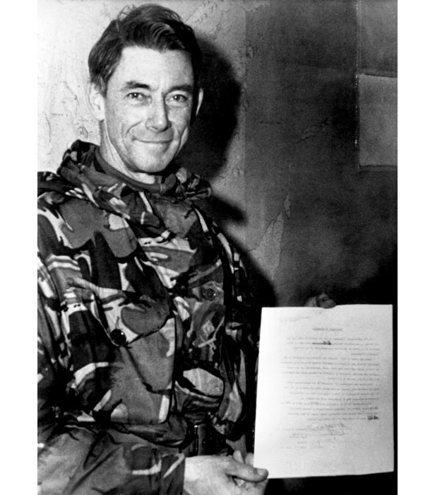 Commander of British Land Forces in the Falklands, Major-General Jeremy Moore, holding the Argentine surrender document.