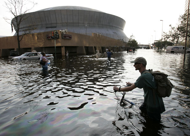 A man pushes his bicycle through flood waters near the Superdome in New Orleans.