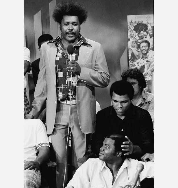 Promoter Don King (standing) with Ali at a pre-fight press conference.