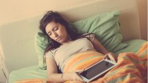 Woman asleep in bed using a tablet