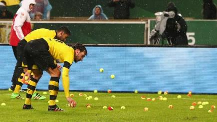 Borussia Dortmund players collect tennis balls thrown on the pitch by fans complaining about ticket prices.