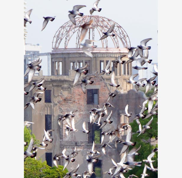 Doves fly by the Atomic Bomb Dome during the ceremony to mark the 63th anniversary of the bombing at Hiroshima Peace Memorial Park in 2008.