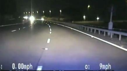 Screengrab from dashcam of car approaching police vehicle while travelling the wrong way down the M6.