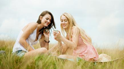 Two woman sitting in field looking at phone