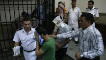 "Egyptian men convicted for ""inciting debauchery"" cover their faces as they leave the defendants' cage in a Cairo courtroom  (AP)"