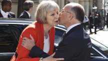 Theresa May is welcomed by French interior minister Bernard Cazeneuve at the emergency meeting (AP)