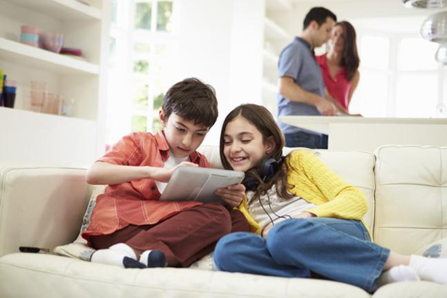 Parents cooking boy and girl on sofa on tablet