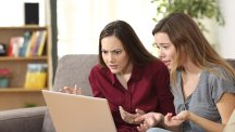 Two women looking at laptop unhappy T