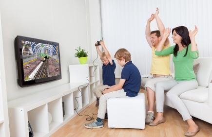 Family playing games console in living room