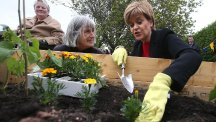 First Minister Nicola Sturgeon plants marigolds during a visit to the Fresh Start Helping Hands project at the Castle Rock Edinvar Housing Association development at the Thistle in Craigmillar, Edinburgh. (PA)
