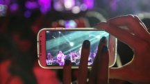 Woman using smartphone to photograph concert