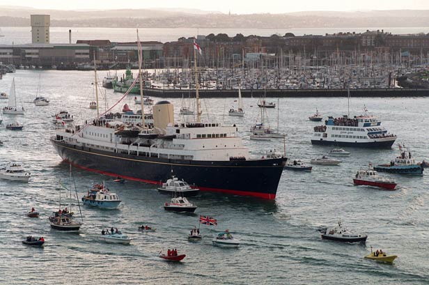A flotilla of small boats greet Britannia as she sails into Portsmouth ahead of decommissioning in 1997.