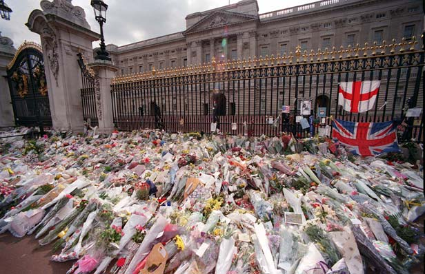Floral tributes begin to gather at the gates of Buckingham Palace.