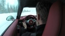 Screen shot of former World Rally champion Walter Rohrl at the wheel of a Porsche 911 on on a frozen lake in Sweden.