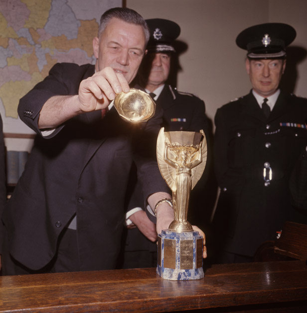 Detective Chief Inspector William Little replaces the top on the recovered World Cup at Cannon Row police station, London.