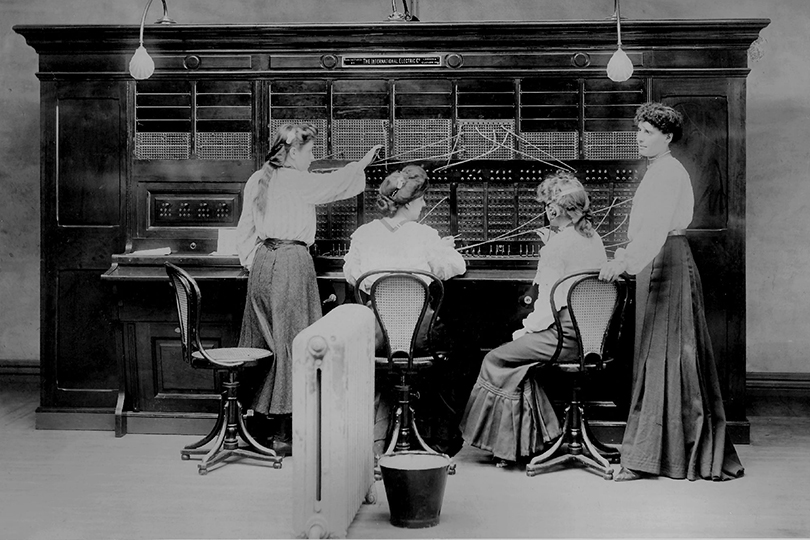 Four Edwardian operators at a manual telephone switchboard. c1902.