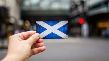 Hand holding a Scottish flag