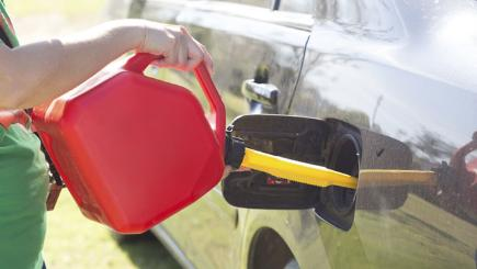 Stock image of a car petrol tank having a liquid added to it from a plastic container.