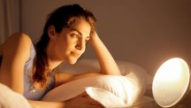 Stock image of woman with a wake-up light.
