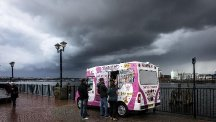 People buy ice-cream from an ice-cream van as huge black storm clouds form over the Cardiff Bay area