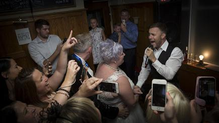 Gary Barlow singing to the couple