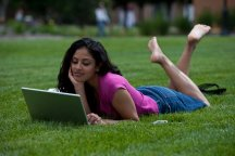 girl on grass looking at laptop