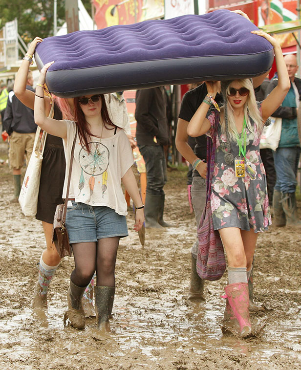 Young women carry a mattress through mud at the Glastonbury Festival 2011