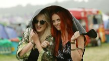 Two young women shelter from the rain under a jacket at Glastonbury Festival