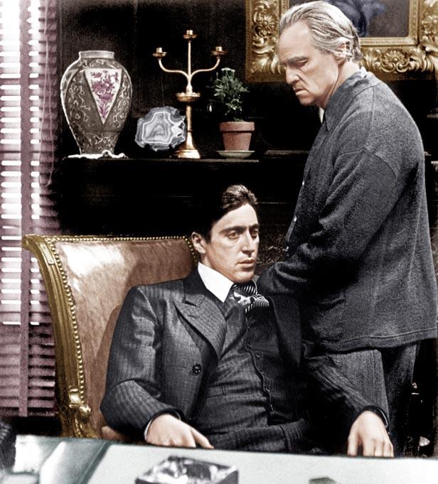 Al Pacino (seated) and Marlon Brando as Michael and Don Vito Corleone.