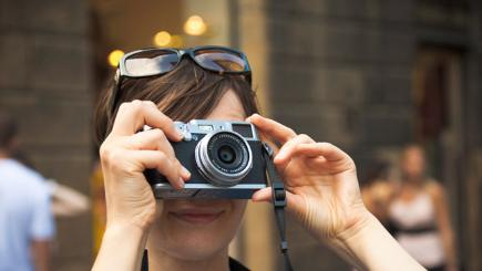 Woman taking photo with compact camera