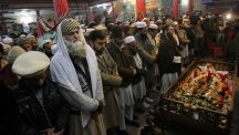 Mourners and relatives of teacher Saeed Khan, killed in the Taliban attack, pray around his body during his funeral procession in Peshawar (AP)