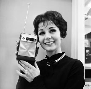 Heartha Constant poses with a new nine-transistor radio