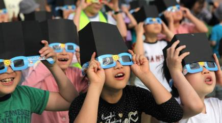 A group of students using solar eclipse viewers (http://home.bt.com/science-news/heres-how-to-stay-safe-during-this-weeks-solar-eclipse-kids-11363968518480)