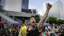 A pro-democracy activist shouts on a street near the government headquarters where protesters have made camp in Hong Kong (AP)