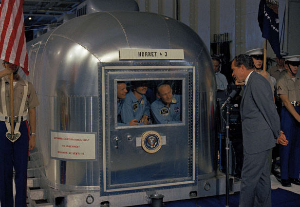 President Nixon meets the Apollo 11 astronauts in their isolation unit aboard the USS Hornet after splashdown and recovery.