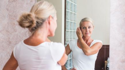 Woman looking at herself in mirror