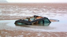 Stock image of a car sinking in low-tide watery sand