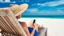 Woman on chair by beach with phone