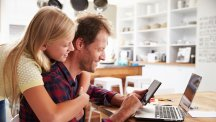 Man and girl on laptop and tablet in kitchen