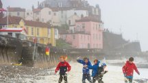 Children play amid sea foam whipped up by high winds on Cromer beach, in Norfolk.